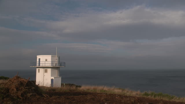 static shot of a coastguard building on top of a cliffed coast - cliff stock videos & royalty-free footage
