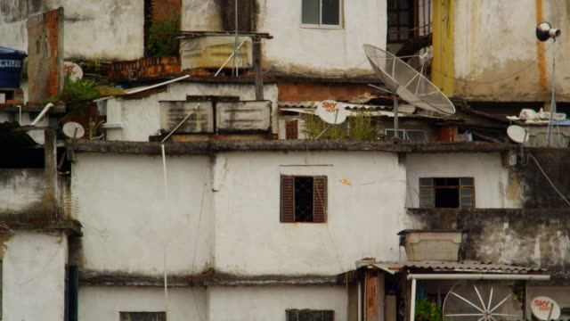Static shot of a favela facade with a kite being flown