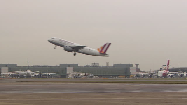 static shot of a germanwings aeroplane during taking off passing through the frame at speed at heathrow airport london - water sports equipment stock videos and b-roll footage