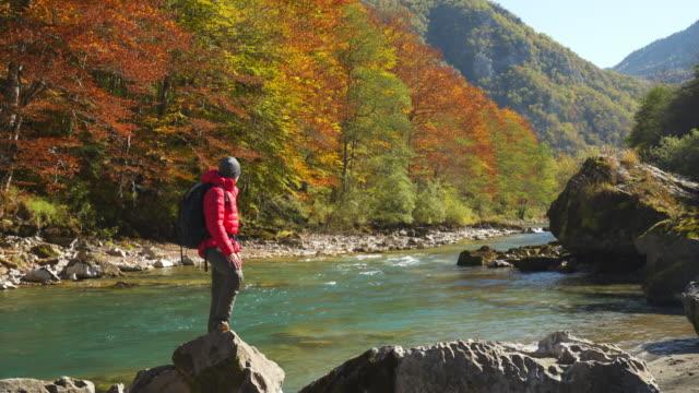 statische aufnahme eines wanderers, der auf einem felsen in der nähe eines flusses mit bunten bäumen steht - rucksack stock-videos und b-roll-filmmaterial