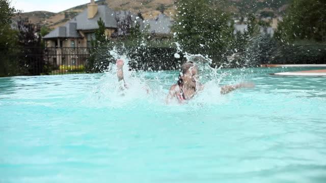 static shot of a little girls splashing in a pool. - schwimmflügel stock-videos und b-roll-filmmaterial