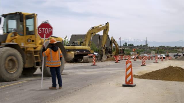vídeos de stock, filmes e b-roll de static shot of a man holding a stop sign and a bulldozer. - equipamento de construção