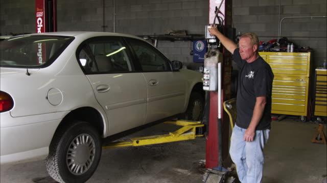 static shot of a mechanic at a car lift. - 歐瑞 個影片檔及 b 捲影像