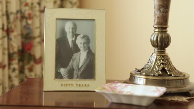 vídeos y material grabado en eventos de stock de a static shot of a picture of a man and a woman on a desk. - marco