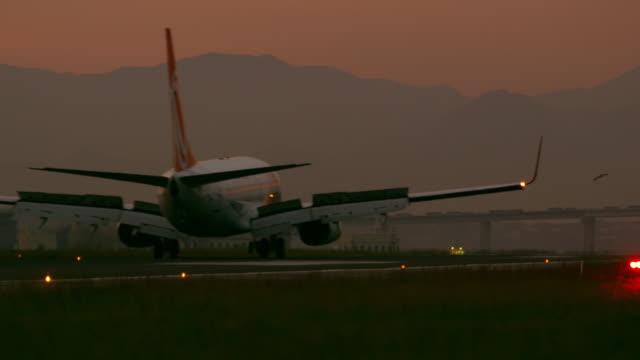 vídeos y material grabado en eventos de stock de static shot of a plane landing in the jacarepaguìá airport with church in background - brasil