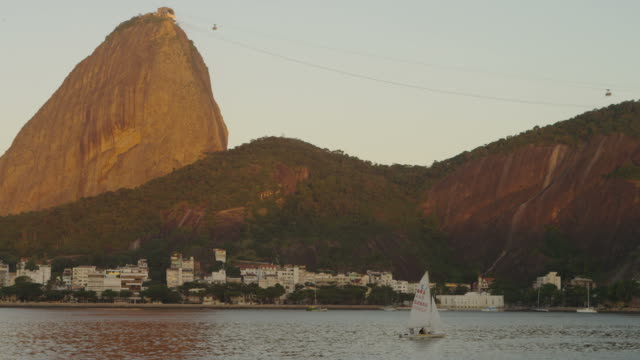 vídeos de stock, filmes e b-roll de static shot of a sailboat on guanabara bay with sugarloaf mountain in the distance. - cable