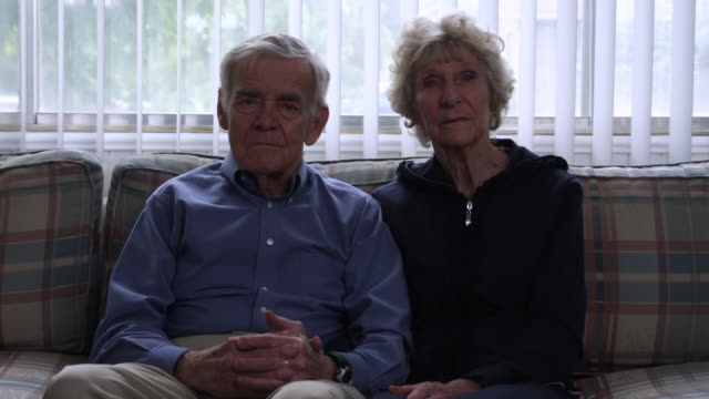 static shot of a senior couple in a living room. - sofa stock-videos und b-roll-filmmaterial