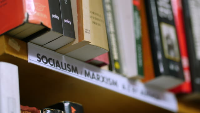 stockvideo's en b-roll-footage met static shot of a 'socialism' sign on a bookshelf - shelf