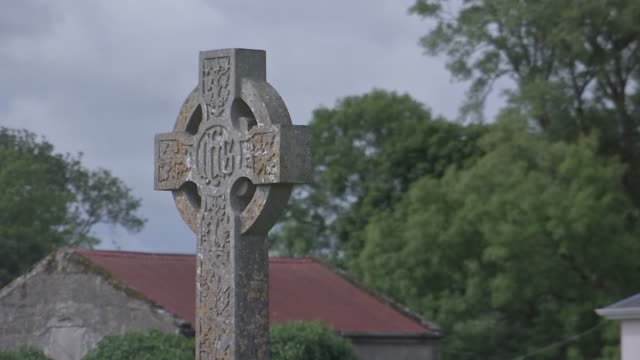 static shot of a stone cross inside of the old cemetery at knock shrine in knock, county mayo, ireland on august 23, 2018. - environment or natural disaster or climate change or earthquake or hurricane or extreme weather or oil spill or volcano or tornado or flooding stock videos & royalty-free footage