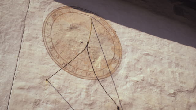 Static shot of a sundial on a wall in Switzerland