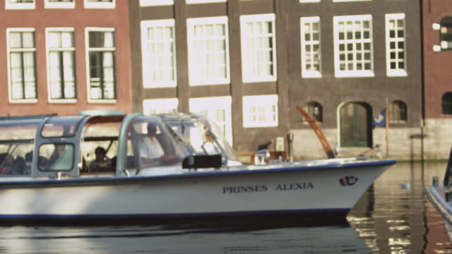 static shot of a tour boat filled with tourists cruising in the amsterdam waterway. - vagare senza meta video stock e b–roll