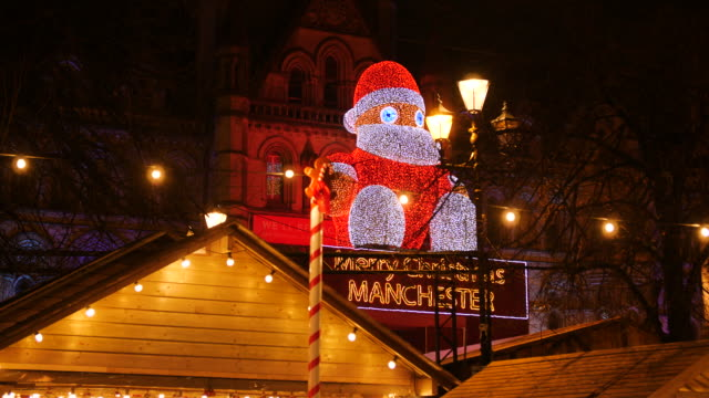 static shot of a 'winter figure' light installation at manchester town hall at night - rathaus stock-videos und b-roll-filmmaterial