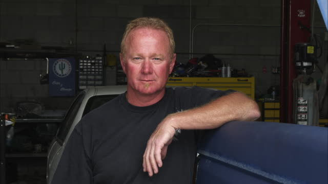 Static shot of an auto mechanic in his shop.