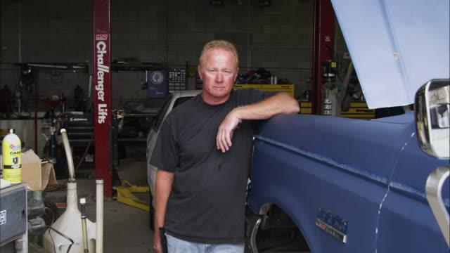 vidéos et rushes de static shot of an auto mechanic leaning on a car in his shop. - capot de voiture