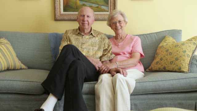 A static shot of an elderly couple sitting close to each other on a grey couch.