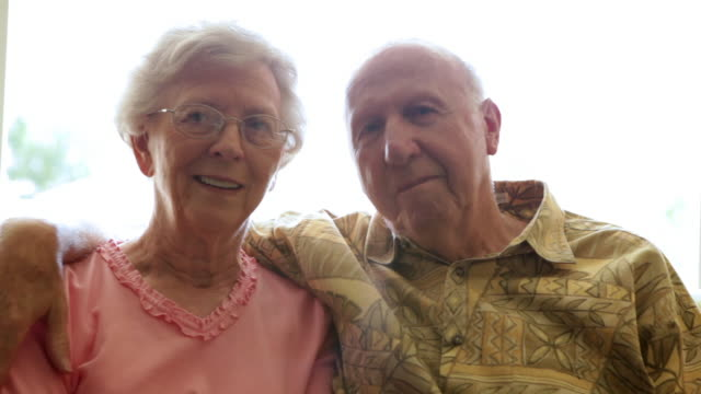 a static shot of an elderly man putting his arm around an elderly woman. - pink shirt stock videos and b-roll footage
