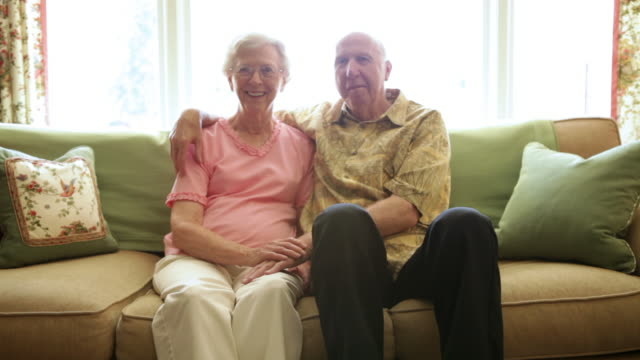 a static shot of an elderly man with his arm around an elderly woman. - pink shirt stock videos and b-roll footage