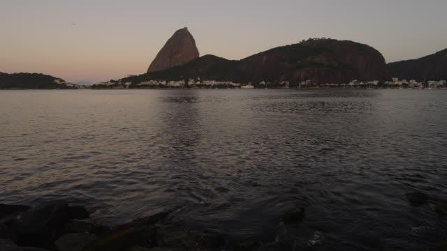 vídeos y material grabado en eventos de stock de static shot of an evening view of the rio coastline with sugarloaf mountain. - 2013