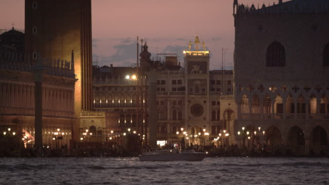 vídeos y material grabado en eventos de stock de static shot of boat passing in front of piazza san marco and the doge's palace, mid evening. - establishing shot