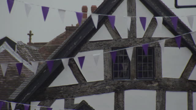 Static shot of bunting strung in front of a timber-framed house in Ludlow in Shropshire fluttering in the wind, UK.