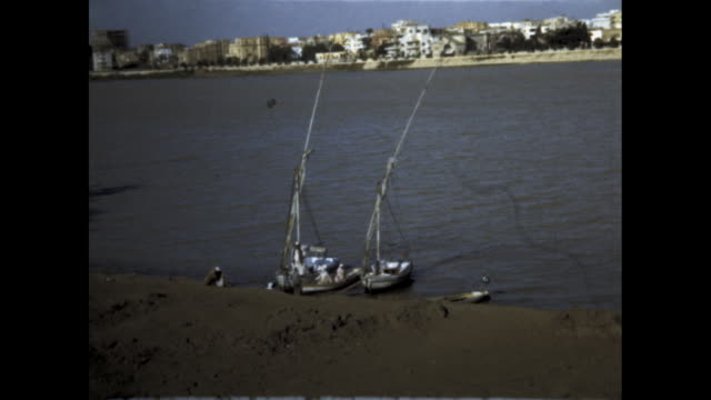 static shot of fishing boats anchored on shore of river - anchored stock videos & royalty-free footage