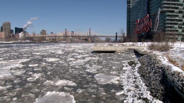 static shot of ice floe on the east river with the iconic pepsi cola sign and queensboro bridge in the background during a record outbreak of arctic... - queensboro bridge stock videos & royalty-free footage
