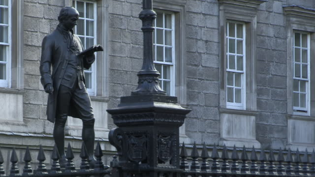 vídeos de stock e filmes b-roll de static shot of john henry foley's statue of oliver goldsmith outside trinity college dublin, republic of ireland. - literatura