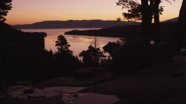 static shot of lake tahoe at sunset with silhouetted trees and flowing river in the foreground - sunset bay state park stock videos & royalty-free footage