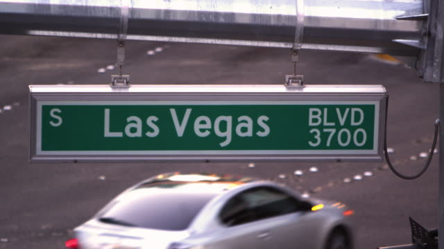 Static shot of Las Vegas street sign with cars passing through.