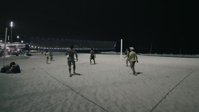 static shot of night volleyball game on copacabana beach. - volleyball net stock videos & royalty-free footage