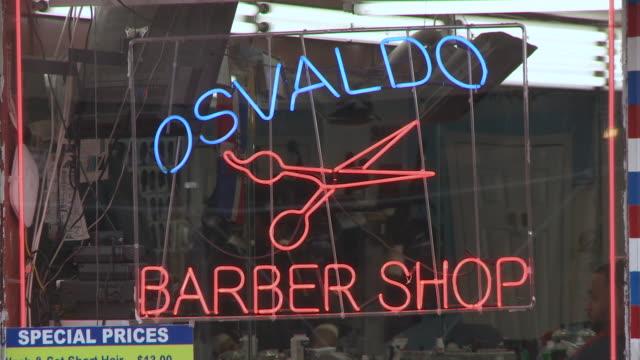 Static shot of Osvaldo Barber Shop in the Bronx during the day showing people inside getting their hair cut as cars pass in front