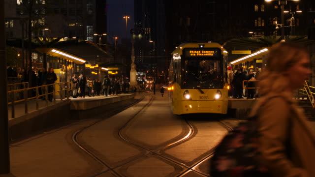 static shot of passengers exiting a tram to etihad campus at st peters square tram stop in central manchester - 通勤電車点の映像素材/bロール
