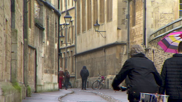 static shot of pedestrians and cyclists moving along brasenose lane, oxford - oxford england stock videos & royalty-free footage