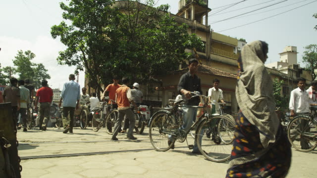 Static shot of people as they wheel bicycles across a level crossing in Guwahati in Assam, India.