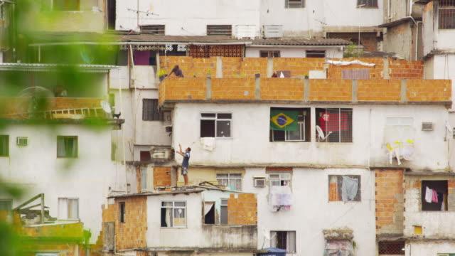 vídeos de stock, filmes e b-roll de rio de janeiro, brazil - june 23: static shot of people on rooftops in favela rio de janeiro, 2013 - pipa brinquedo