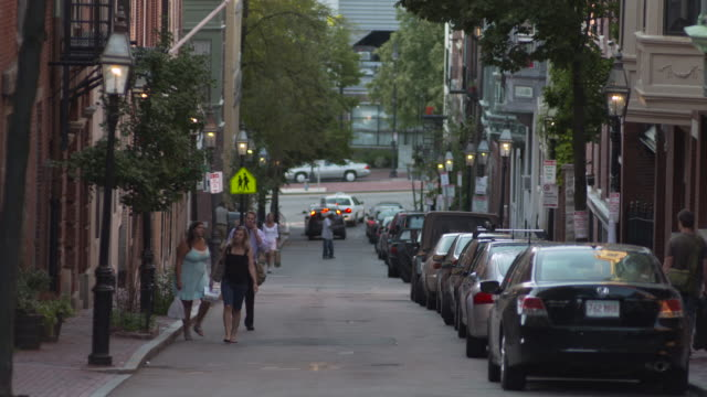 static shot of people walking up a hill on a summer's evening, boston, massachusetts, usa. - erkerfenster stock-videos und b-roll-filmmaterial