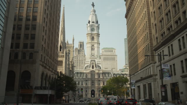 Static shot of Philadelphia City Hall between tall surrounding buildings, Pennsylvania, USA.