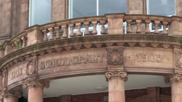 Static shot of pigeons flying past the porch of the Burslem School of Art, Stoke-on-Trent, UK.