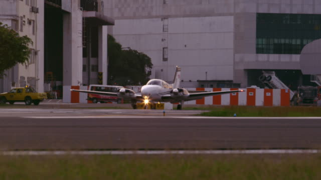 Static shot of plane taxis on tarmac in front of buildings at JacarepaguÌÁ Airport