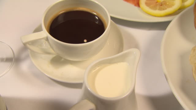 static shot of quivering coffee with a jug of cream next to other foods on a table. - coffee cup stock videos & royalty-free footage