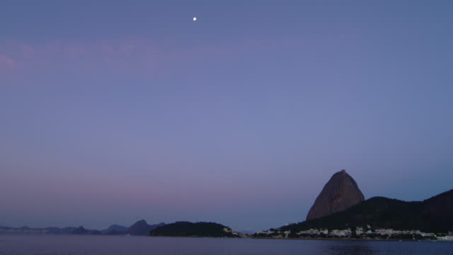 static shot of rio's sugarloaf mountain in the distance beyond a dark ocean. - 2013 stock videos & royalty-free footage