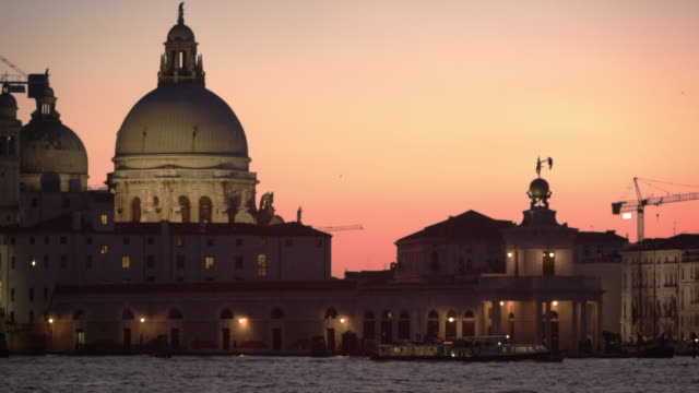 Static shot of Santa Maria della Salute and boats in the canal at sunset.