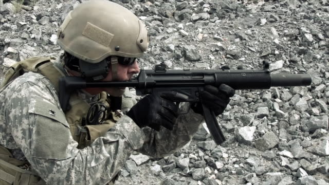 Static shot of soldier shooting automatic small target rifle at range while kneeling.