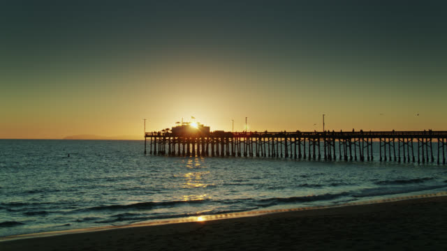 static shot of sun setting behind newport beach pier - channel islands california stock videos & royalty-free footage
