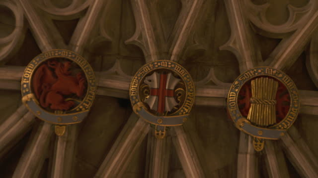 Static shot of symbolic motifs on the ceiling of St George's Chapel Windsor Castle including a dragon the St George's Cross and a sheath of wheat...