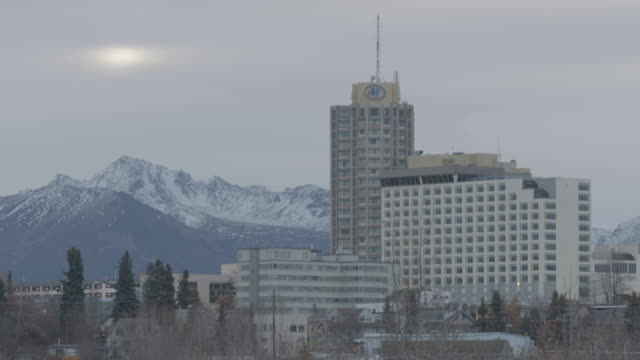 static shot of tall buildings in anchorage with mountains in the background - anchorage alaska stock videos and b-roll footage