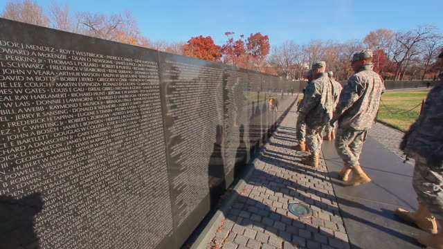 a static shot of the back of a group of soldiers slowly walking by the vietnam war memorial. - vietnam veterans memorial video stock e b–roll