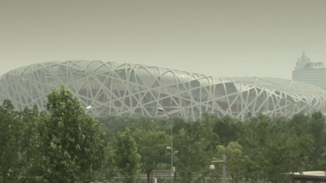 Static shot of the Beijing National Stadium behind trees, China.