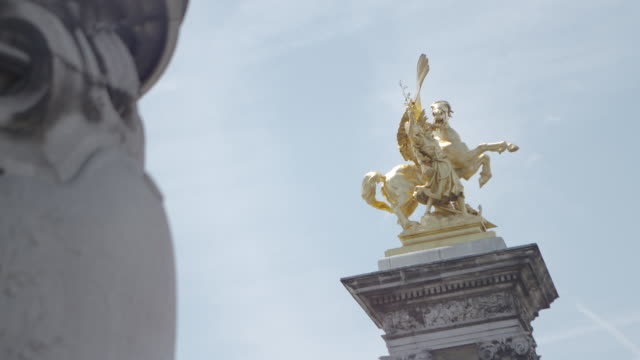static shot of the gold statue 'renommee des sciences' on the pont alexandre iii in paris, france - pont alexandre iii stock videos & royalty-free footage