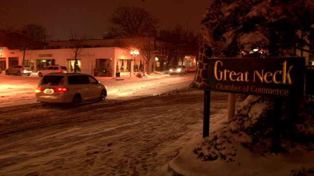 Static shot of the Great Neck NY sign as a snow plow clears snow from the street